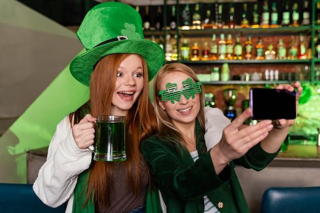 Freundinnen feiern st. patrick's tag an der bar und selfie zusammen mit getränken
