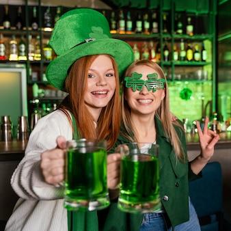 Freundinnen feiern st. patricks tag an der bar mit getränken