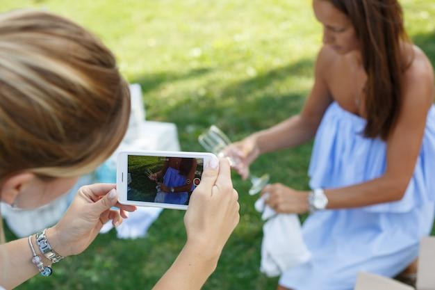 Freundinnen fotografieren am telefon während sie sich auf ein picknick vorbereiten