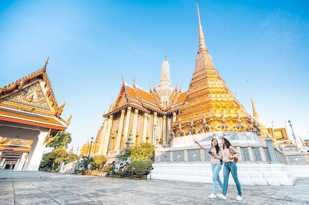 Freundinnen genießen besichtigung während der reise im tempel des smaragdbuddhas in thailand