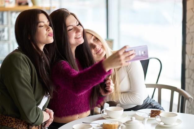 Freundinnen haben spaß im café, trinken tee und machen selfie