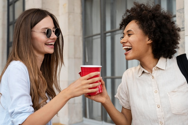 Freundinnen haben spaß zusammen im freien mit plastikbechern