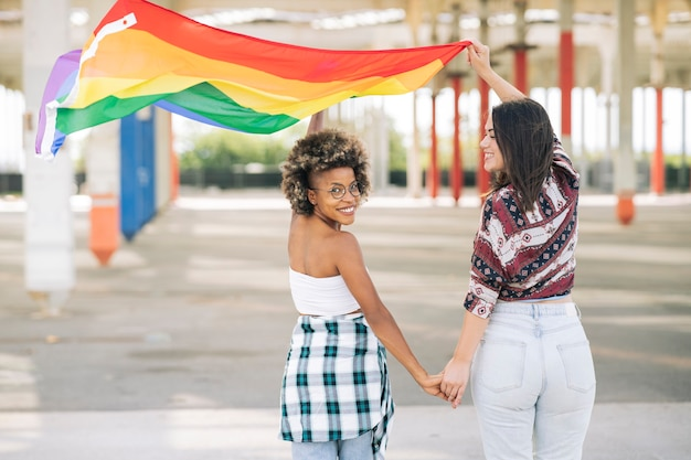 Freundinnen halten händchen beim gehen mit einer lgbt-flagge