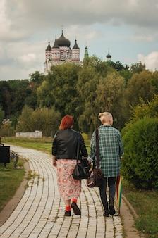 Freundinnen halten händchen und gehen im park spazieren, ein junges lesbisches paar geht mit einem regenbogenregenschirm im freien spazieren