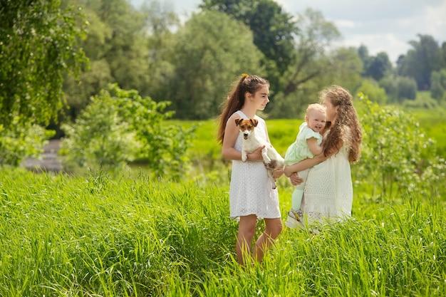 Freundinnen im teenageralter auf einem spaziergang mit ihrer schwester und ihrem hund
