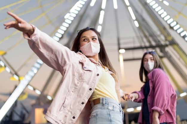 Freundinnen im vergnügungspark mit medizinischen masken