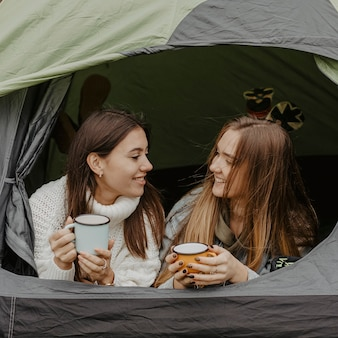 Freundinnen im zelt plaudernd mit tasse tee