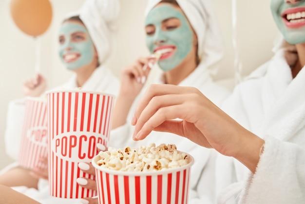 Freundinnen in bademänteln, die popcorn essen.