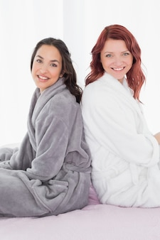 Freundinnen in den bademäntel, die rücken an rücken auf bett sitzen