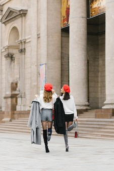 Freundinnen in roten baskenmützen ziehen durch die stadt, gehen spazieren, lachen und genießen das leben.