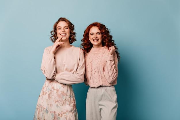 Freundinnen lachen vor der kamera. studioaufnahme der erstaunlichen stilvollen mädchen, die auf blauem hintergrund stehen.