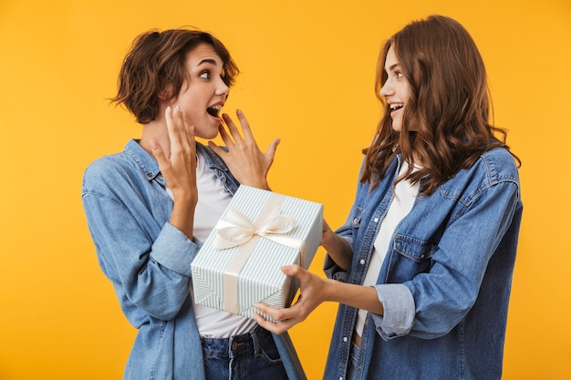 Freundinnen lokalisiert über gelbe wand, die überraschungsgeschenkbox vorhanden hält.