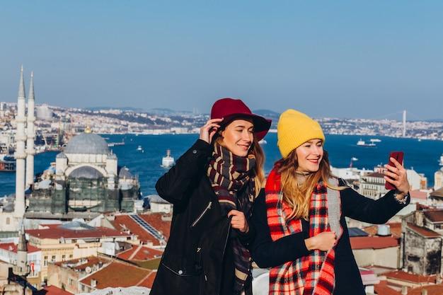 Freundinnen machen ein selfie auf dem dach des großen basars, istanbul, türkei. zwei lächelnde mädchen werden am telefon vor dem hintergrund von istanbul an einem klaren wintertag fotografiert.