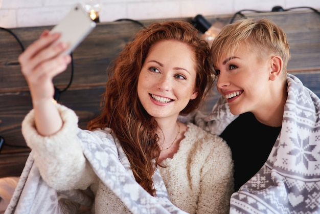 Freundinnen machen ein selfie im schlafzimmer