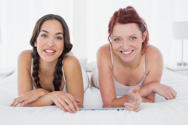 Freundinnen mit der digitalen tabelle, die im bett liegt
