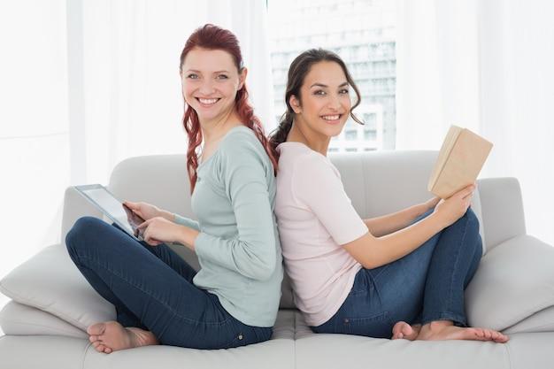Freundinnen mit digitaler tablette und buch zu hause