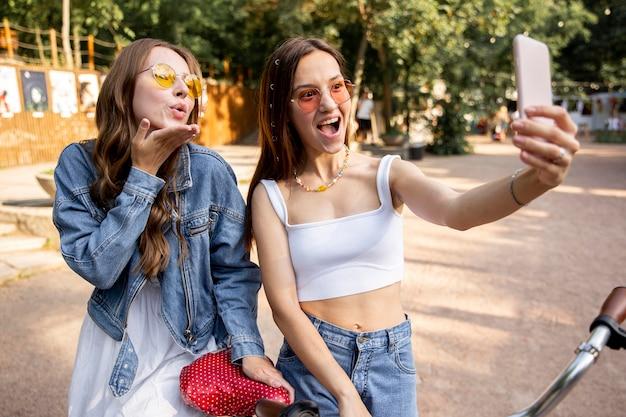 Freundinnen mit fahrrad machen selfies