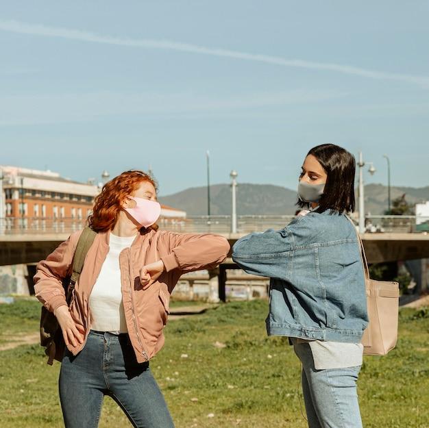 Freundinnen mit gesichtsmasken im freien, die den ellbogengruß tun
