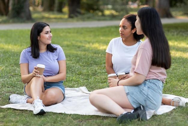 Freundinnen mit kaffee zusammen im park