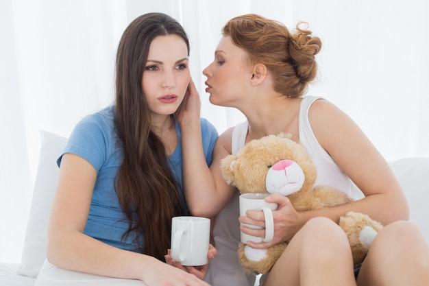 Freundinnen mit kaffeetassen, die im bett klatschen