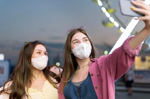 Freundinnen mit masken, die selfie am vergnügungspark nehmen