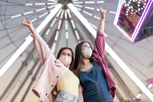Freundinnen mit masken im vergnügungspark
