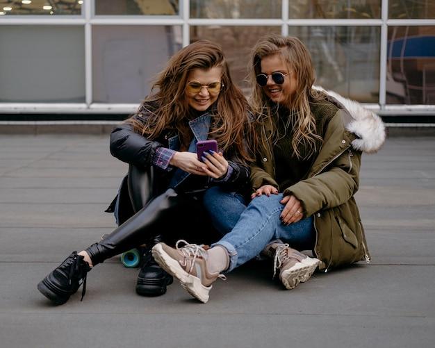 Freundinnen mit smartphone, die spaß zusammen im freien haben