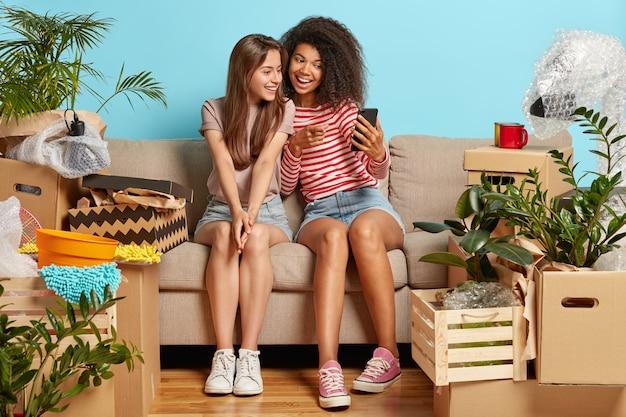 Freundinnen sitzen auf der couch, umgeben von kisten