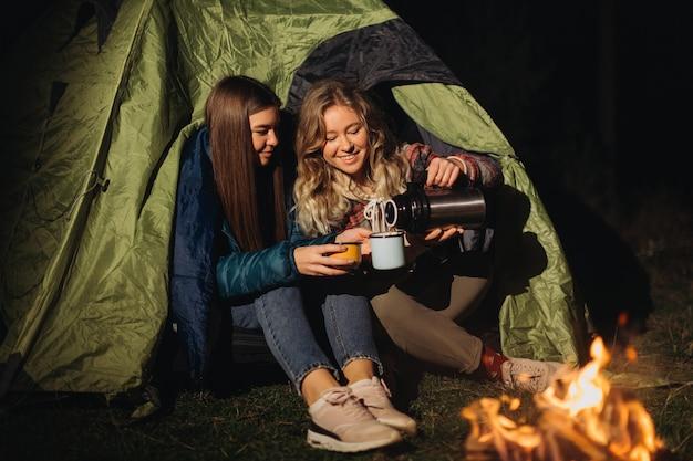 Freundinnen sitzen im zelt und trinken nachts tee