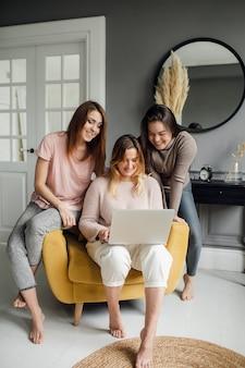 Freundinnen studenten erledigen aufgaben zusammen auf einem laptop zu hause hochwertiges foto