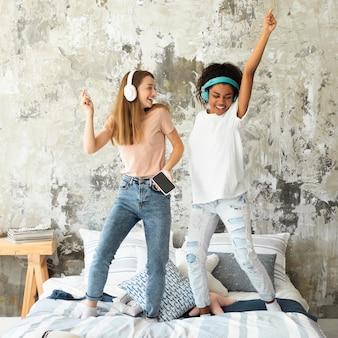 Freundinnen tanzen im bett, während sie musik über kopfhörer hören