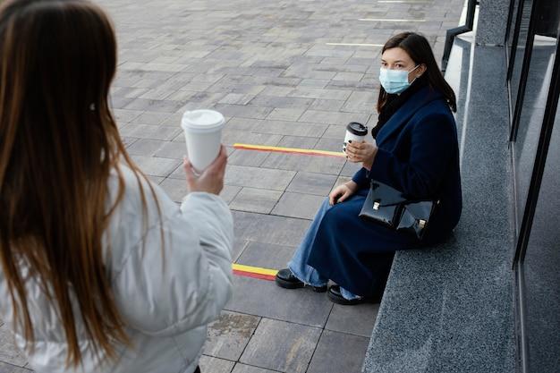 Freundinnen treffen sich beim kaffee, während sie masken tragen