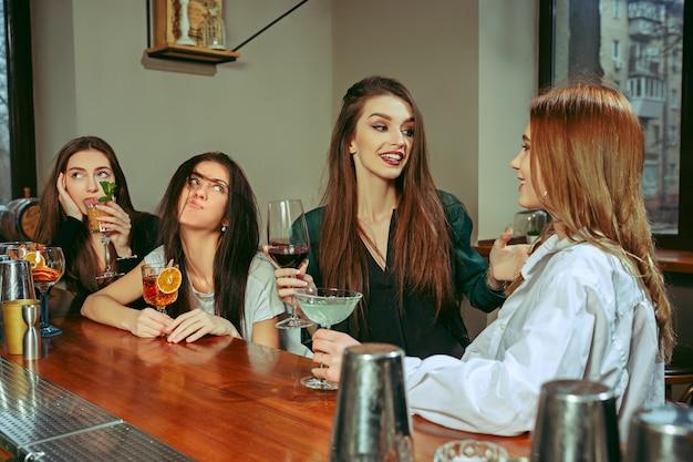 Freundinnen trinken an der bar. sie sitzen an einem holztisch mit cocktails. sie tragen freizeitkleidung.