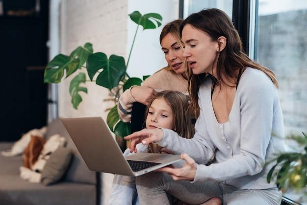 Freundinnen und ein kleines mädchen sitzen zu hause auf einer fensterbank und schauen sich einen film auf einem laptop an.