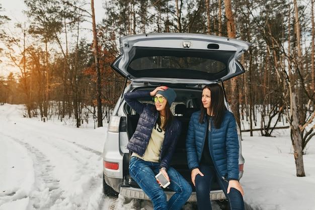 Freundinwinterabnutzung schneebedecktes tageswinter-waldauto