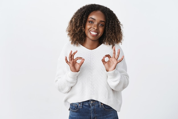 Freundlich aussehende, fröhliche, süße afroamerikanische pralle frau, die erfreut lächelt, zeigt in ordnung, ok genehmigungsgeste wie service empfehlen gute arbeit, sagen sie kein problem, versichern sie, dass sie in ordnung ist, weiße wand?