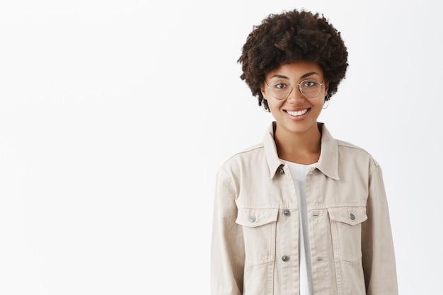 Freundlich aussehende lässige junge dunkelhäutige frau mit afro-frisur in brille und trendigem hemd, die breit lächelt und über grauer wand mit sorglosem und entspanntem blick steht