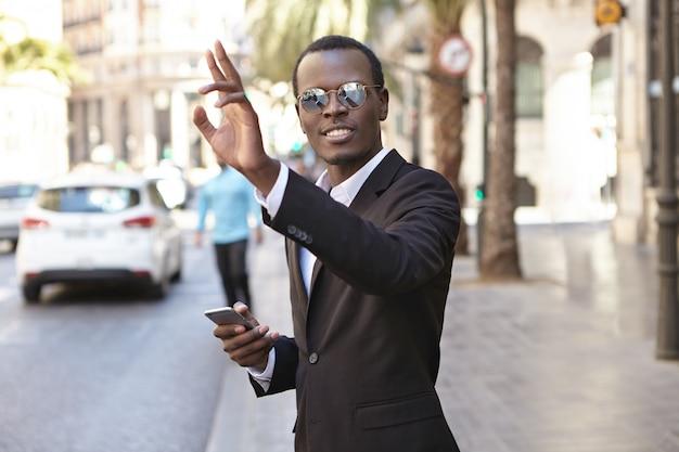 Freundlich aussehender erfolgreicher junger afroamerikanischer unternehmer im eleganten schwarzen anzug und in der brille, die sms auf handy und hand anheben, während taxi heraufhagend, auf straße in der städtischen umgebung stehend