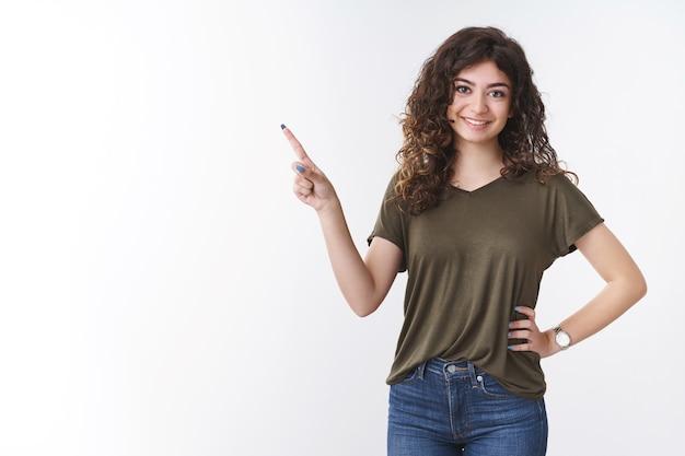 Freundlich aussehendes, charmantes, entschlossenes, süßes armenisches mädchen, das eine rede zeigt, zeigt kollegen, die auf die obere linke ecke zeigen, die selbstbewusste entspannte pose stehen und weitgehend selbstbewusst lächeln