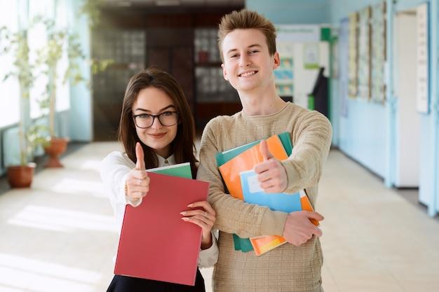 Freundlich gut aussehende studenten innerhalb der universität mit ordnern, büchern, schulheften