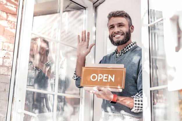 Freundlich sein. erfreuter freundlicher mann, der mit seiner hand winkt, während er in sein café einlädt Premium Fotos