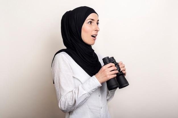 Freundlich überraschte junge muslimische frau im weißen hemd und im hijab hält fernglas