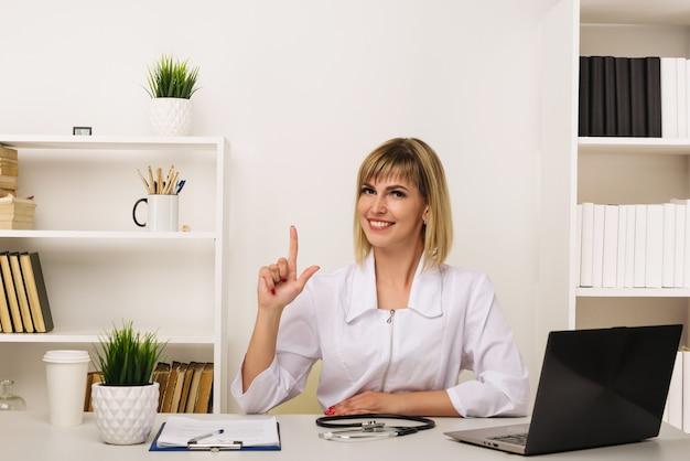 Freundliche ärztin arbeitet an ihrem schreibtisch im büro und zeigt nach oben