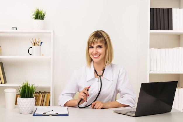 Freundliche ärztin arbeitet an ihrem schreibtisch im büro