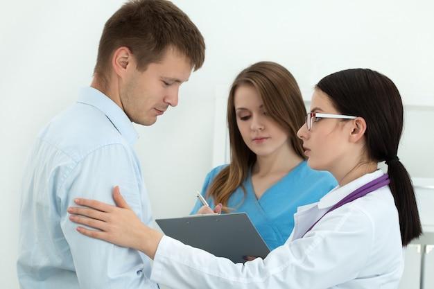 Freundliche ärztin, die den arm des männlichen patienten berührt, um ermutigung, empathie und unterstützung zu erhalten
