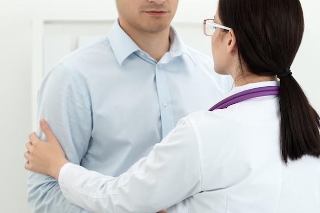 Freundliche ärztin, die den arm des männlichen patienten für ermutigung und empathie berührt. konzept für partnerschaft, vertrauen und medizinische ethik. verminderung und unterstützung von schlechten nachrichten. patientenjubel und unterstützung