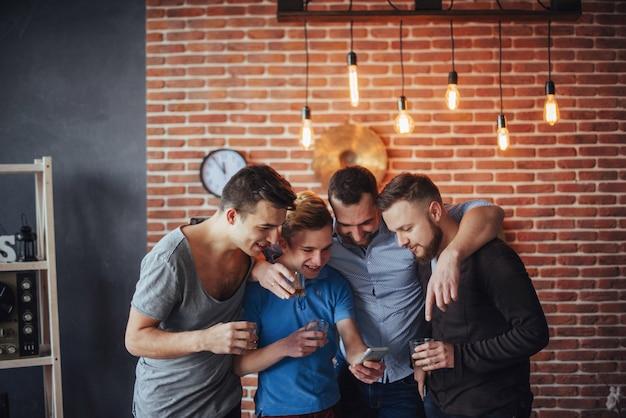Freundliche alte freunde verständigen sich miteinander und rufen uhr, gläser whisky in der kneipe an. unterhaltungslebensstil. wifi verbundene leute in der bartabellensitzung