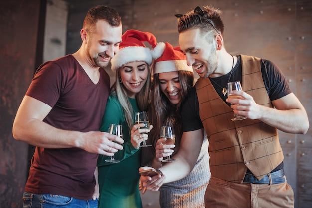 Freundliche alte freunde verständigen sich miteinander und rufen uhr, mit gläsern champagner in der partei des neuen jahres an. konzept der unterhaltung und des lebensstils. wifi verbunden menschen