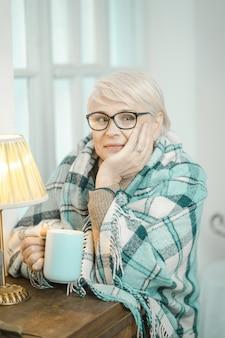 Freundliche alte oma, die über etwas nachdenkt und tee trinkt