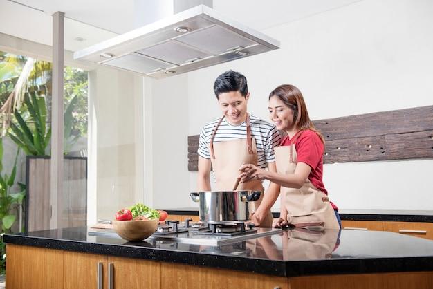 Freundliche asiatische paare, die zusammen kochen